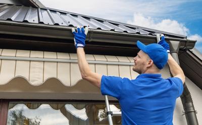 A serviceman performing Gutter Installation in Peoria IL