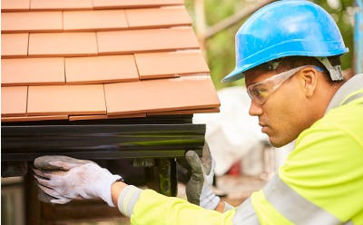 Worker carefully performing Gutter Replacement in Peoria IL