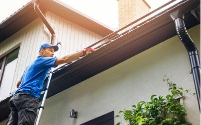 A technician performing Gutter Cleaning in East Peoria IL