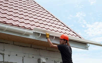 A technician installing Gutters in Peoria IL